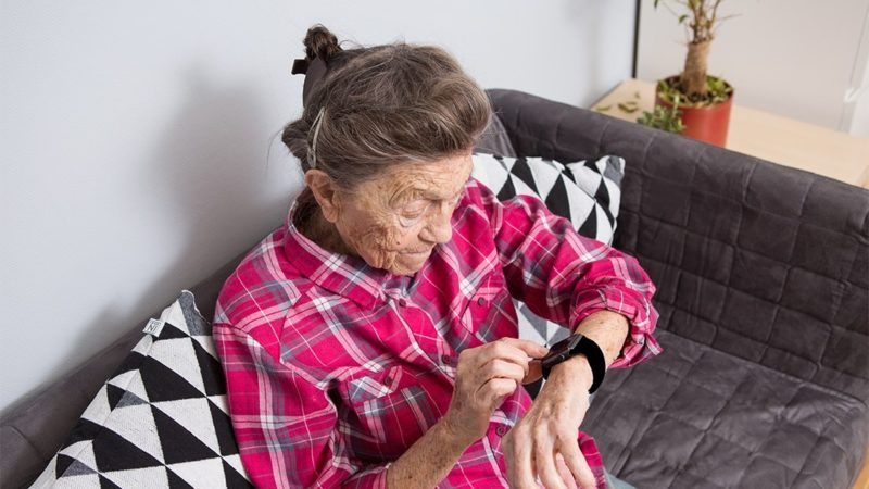 A very old senior Caucasian grandmother with gray hair and deep wrinkles sits at home on the couch in jeans and a red plaid shirt and uses a smart watch on her wrist. Pensioner and technology.