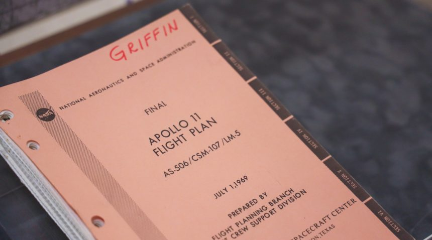 A copy of the final revision of the Apollo 11 flight plan signed by Gerald D. Griffin in a display case.
