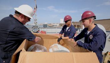Staff and cadets from the Texas A&M Maritime Academy prepare to unload NOAA buoys