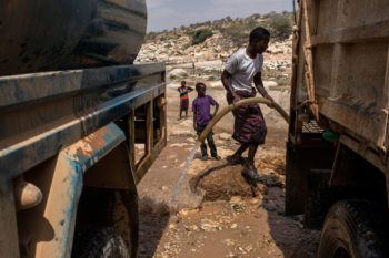 Men fill trucks with water from a nearly dried up riverbed on February 24, 2017 in Dhudo, Somalia