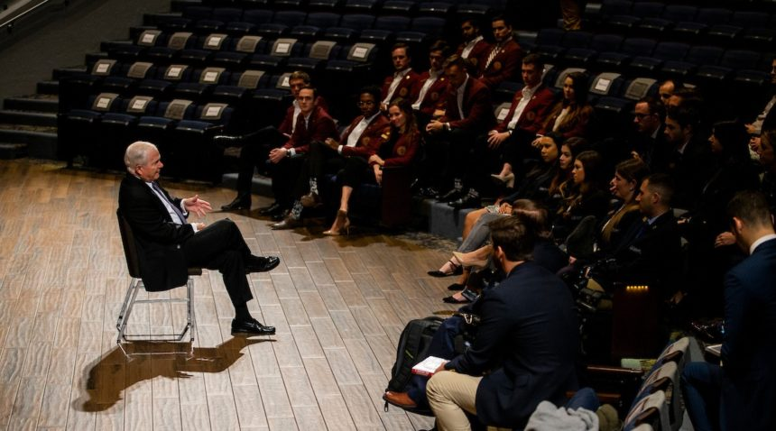 Robert Gates seated before students in an auditorium