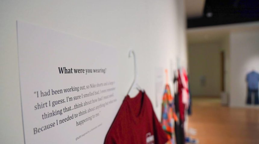 A story from a sexual assault survivor displayed next to a hanging T-shirt