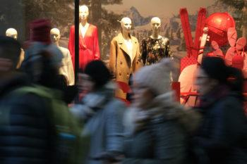 People walk past mannequins in a clothing retailer display window