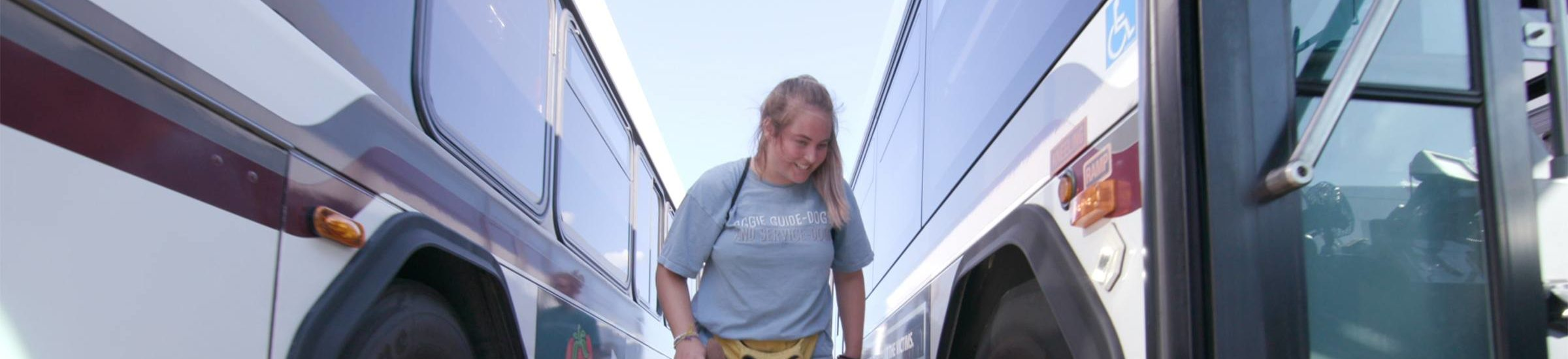 Student dog trainer steps onto bus with service dog
