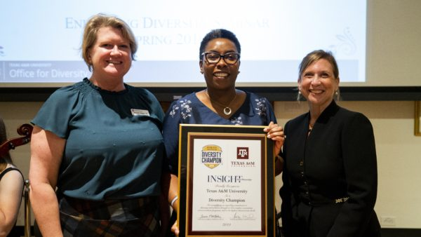 Jennifer Reyes, Robin Means-Coleman and Holly Mendelson pose with the framed Diversity Champion Award