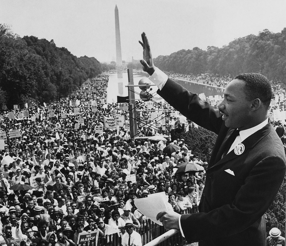 A black and white photo of Dr. King waving to the crowd at the March On Washington