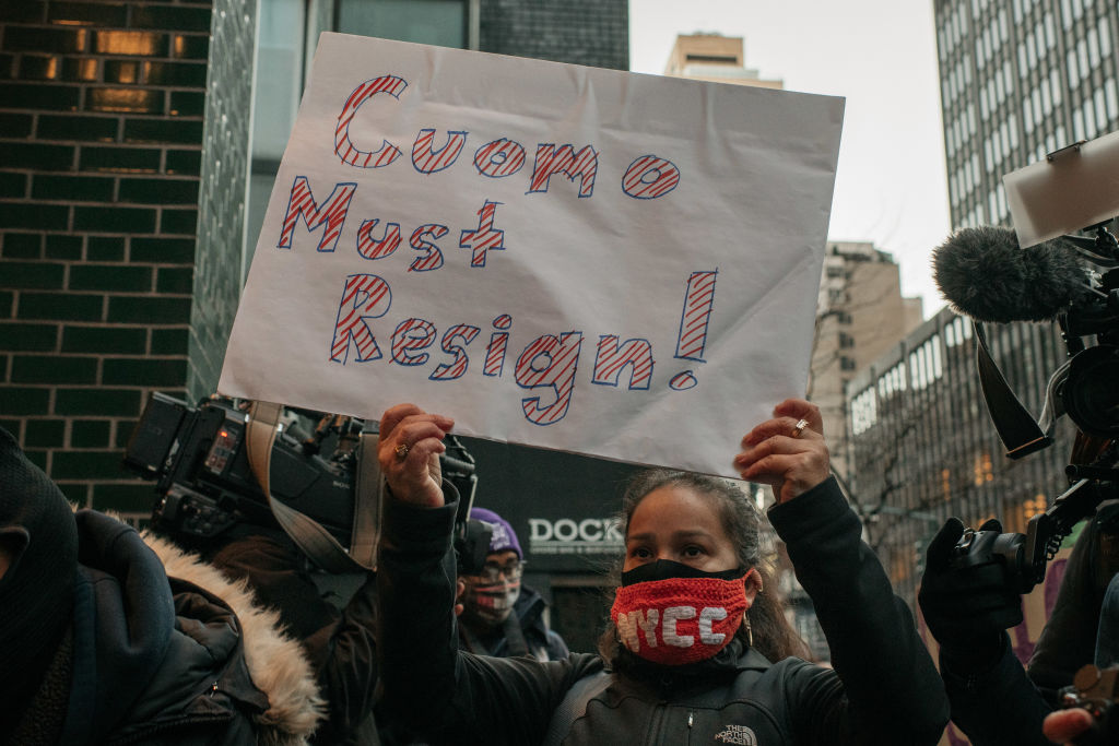 """a woman holds a sign that says """"Cuomo must resign!"""""""