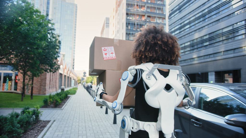 woman wears a lower back exoskeleton device while carrying a moving box down a sidewalk