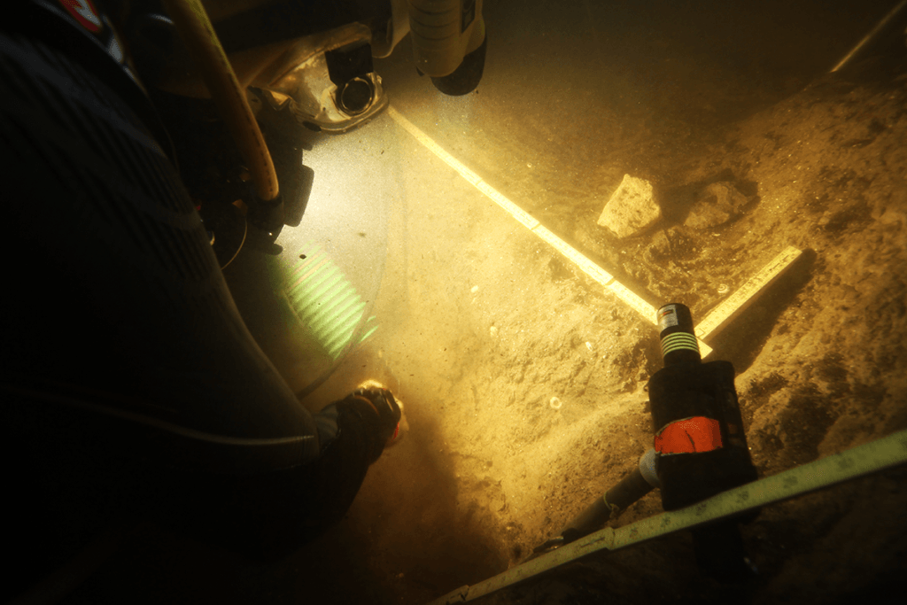 a diver in murky shines a light on artifacts