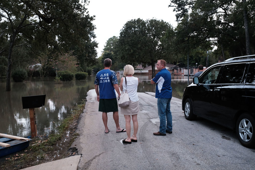 HOUSTON, TX - SEPTEMBER 04: People stand in a flooded neighborhood as Texas moved toward recovery from the devastation of Hurricane Harvey on September 4, 2017 in Houston, Texas. Almost a week after Hurricane Harvey ravaged the city, some neighborhoods still remained flooded and without electricity.