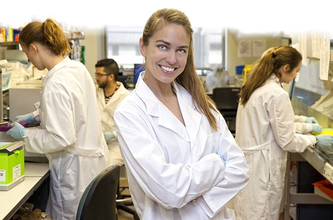 Sarah Hamer posing in her lab coat for the picture with her arms crossed