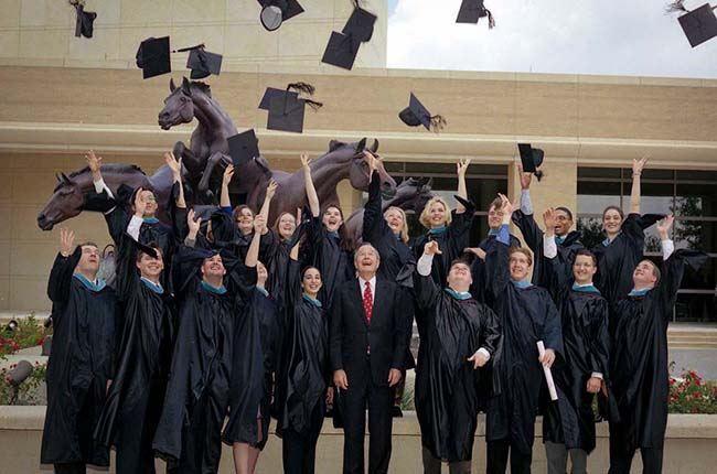 President Bush celebrates with graduates of the Bush School in May 2002.